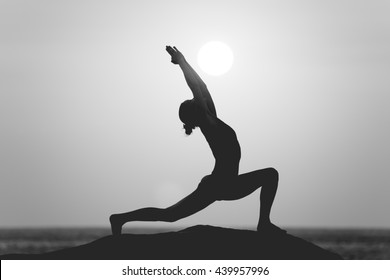 Warrior pose from yoga by woman silhouette on sunset in black and white style filter