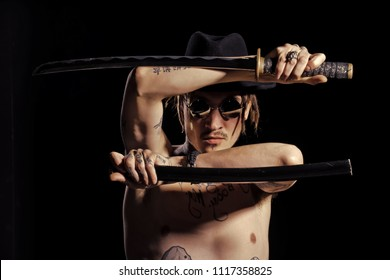 warrior of Samurai. Warrior posing with sword with tattooed hands, neck and chest on black background. Defense, honor, torture, punishment, harakiri, tattoo concept.