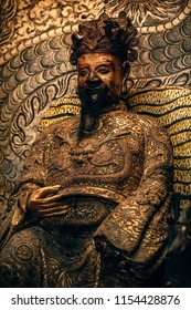 Warrior statue in a moody pose is sitting inside of a Chinese temple in Penang Malaysia. Statue with the golden robe and dark golden face is sitting with background wall with detail design pattern.
