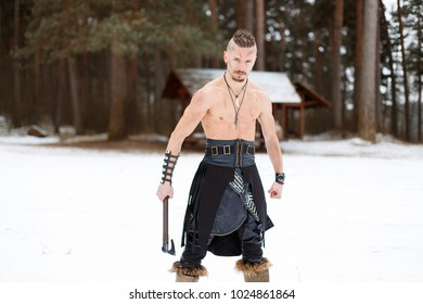 Warrior Viking with an Ax with a Naked Torso in the Winter Forest