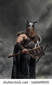 Warrior Viking in full arms with axe and shield on dark background