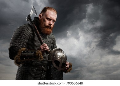 Warrior Viking in full arms with axe and helmet on dark background