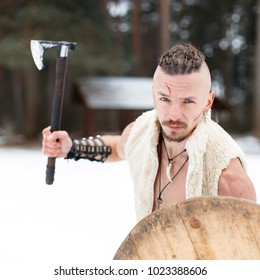 Warrior Viking with a scar with an ax and a wooden shield in the woods on a winter day