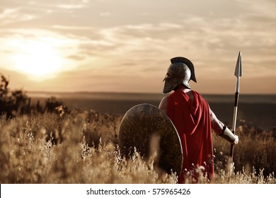 Warrior wearing iron helmet and red cloak.
