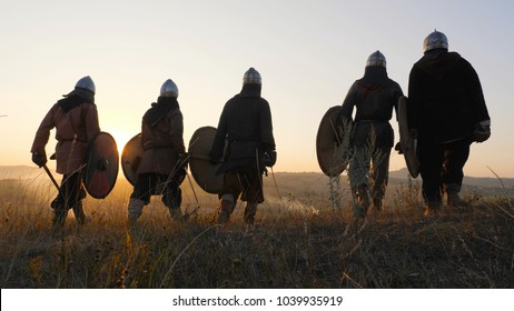 Warriors vikings stand in field and look at beautiful sunset on the battle field. Medieval Reenactment.Contre-jour. Back view.
