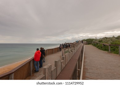 WARRNAMBOOL, AUSTRALIA - JUNE 11 2018: Tourists using the whale watching platform at Logan's Beach, Warrnambool, Victoria, Australia.