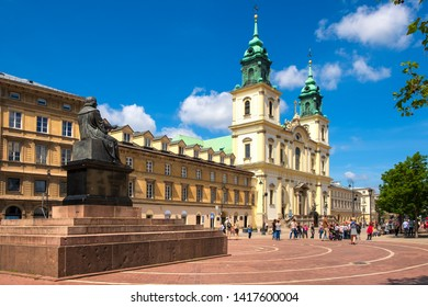 Warsaw, Mazovia / Poland - 2019/06/01: Front view of the baroque Holy Cross Church and the Mikolaj Kopernik statue, at the Krakowskie Przedmiescie street in the Old Town quarter of Warsaw