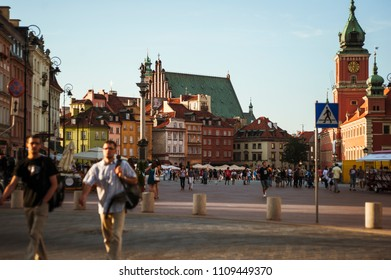 Warsaw old town/people walking the streets of Warsaw with the rebuilt old town panorama in the background. Warsaw, Poland, August 17, 2011.
