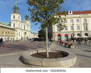 Warsaw, Poland - 09.11.2019: Copernicus Square, green tree and a building with a cathedral with crosses in the early morning