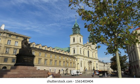 Warsaw, Poland - 09.11.2019: near the monument to Copernicus on the background of a green tree and a building with a cathedral with crosses in the early morning