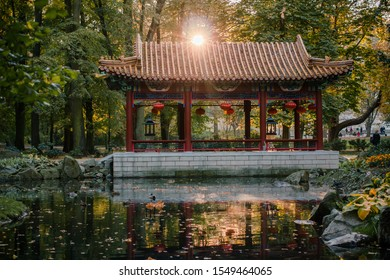 Warsaw, Poland, 10 october 2019. Chinese pavilion and temples at the Chinese Garden at Lazienki Park. Sunset in autumn Chinese Garden with Pagoda and Pond .