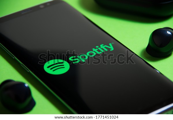 Warsaw, Poland - 10.06.2020: Spotify app on the smartphone. Music streaming. Surrounded by true wireless earbuds. Listening to music with Galaxy Buds - TWS.