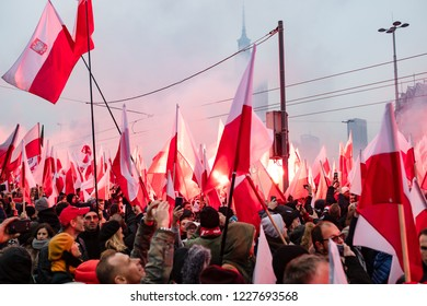 Warsaw / Poland - 11.11.2018: The Independece March. nationalists faces flags and symbols. National independence day, 100th anniversary.