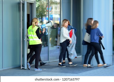 Warsaw, Poland. 15 October 2018. Evacuation of an office building. People exit the building on exit door.