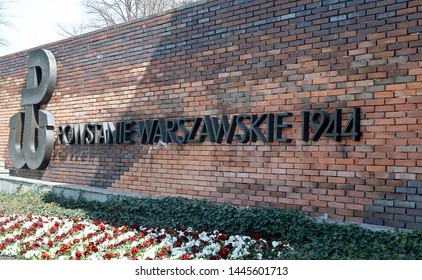 WARSAW, POLAND - 16 APRIL 2019: Light and shadows fall on the rear brick wall of the 1944 Warsaw Uprising Monument in Krasinski Square with red and white pansies, the Polish colours, in front.