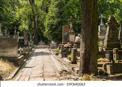 Warsaw Poland 5/18/18: Pathway  at the historical Powazki cemetery. Tombstones and trees on both sides of the path.
