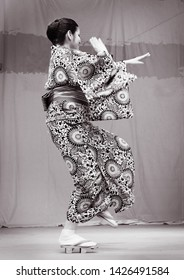 """Warsaw Poland, 6/15/19: Open air Japanese Festival in the park -  dancer lady in kimono and flip-flops dances Bon-odori  dance characteristic for the All Saint Day called in Japan """"Obon Festival"""""""
