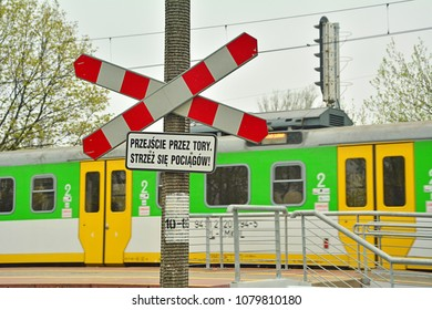 WARSAW, POLAND - APRIL 17, 2018 0 Railway pedestrians level crossing for with a saltire (Saint Andrew's Cross) in Poland with a Koleje Mazowieckie train in the background