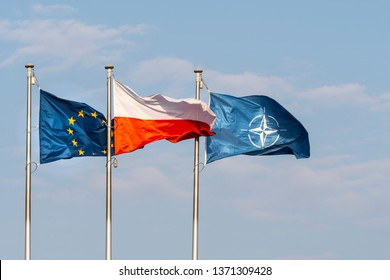 Warsaw, Poland. April 2019.   The flags of Poland, Europe and NATO waving on a blue sky