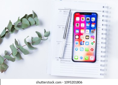 WARSAW, POLAND - APRIL 24, 2018: New Iphone X modern mobile phone on white desk, styled flat lay scene