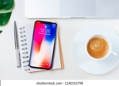 WARSAW, POLAND - APRIL 24, 2018: New Iphone X modern mobile phone on white working desk with coffee