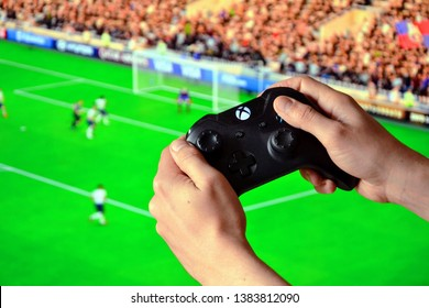 Warsaw, Poland - April 27 2019: Man's hands holding XBOX ONE controller, (game pad). Blurred background with FIFA game. Football, soccer game on the screen