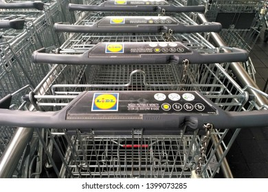 Warsaw, Poland  - April 27 2019: Line of shopping carts in Lidl supermarket. Lidl sign at shopping carts. Lidl shopping cart with information - what coin or token put in to unlock it.