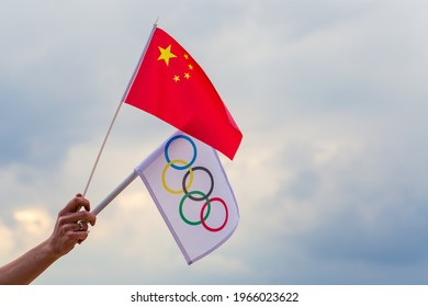 Warsaw, Poland - April 29, 2021: Fan waving the national flag of China and the Olympic flag.