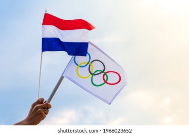 Warsaw, Poland - April 29, 2021: Fan waving the national flag of Netherlands and the Olympic flag.