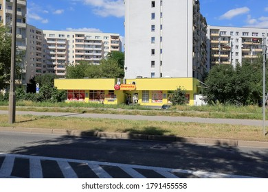 Warsaw, Poland - August 05, 2020: Small building that houses a well know grocery store is nearby residential buildings of Goclaw housing estate.