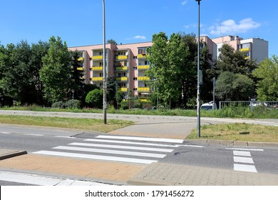 Warsaw, Poland - August 05, 2020: Residential building surrounded with trees is visible across the street. This apartment building is a part of a housing estate which is called Goclaw.