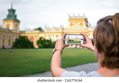 WARSAW, POLAND - AUGUST 11: A young woman photographing the royal Wilanow Palace in Warsaw.