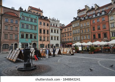 WARSAW / POLAND - AUGUST 15 2012: People look at sketches, paintings, watercolors and other artwork on display on A-frames in the Old Town Market Place square, near the old water fountain.
