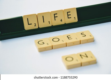 Warsaw, Poland - August 19 2018: Scrabble letters spelling the message: Life goes on. Scrabble tiles on the stand