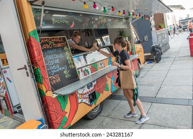WARSAW, POLAND - AUGUST 2: Woman buys Mexican food during Food Truck festival on August 2, 2014 in Warsaw