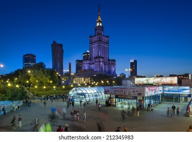 WARSAW, POLAND - AUGUST 20, 2014: Undefined people in the center of Warsaw during the night. The Palace of Culture and Science building is a landmark of capital Poland.