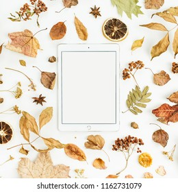 WARSAW / POLAND - AUGUST 20, 2018: Blank screen tablet iPad by Apple with dry fall autumn leaves, petals and oranges on white background. Flat lay, top view seasonal concept.