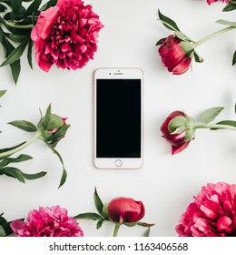 WARSAW / POLAND - AUGUST 20, 2018: iPhone 8 Plus by Apple in frame of pink peonies flowers on white background. Flat lay, top view mock up.