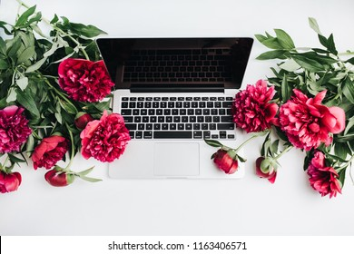 WARSAW / POLAND - AUGUST 20, 2018: Laptop Macbook Pro by Apple and pink peonies flowers on white background. Flat lay, top view summer background.