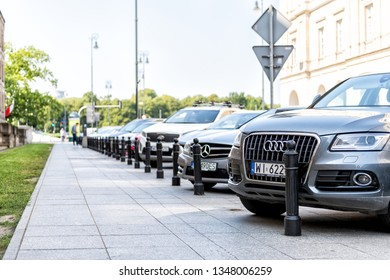 Warsaw, Poland - August 23, 2018: Closeup of in town street during sunny summer day and cars parked in parking lot with audi and mercedes