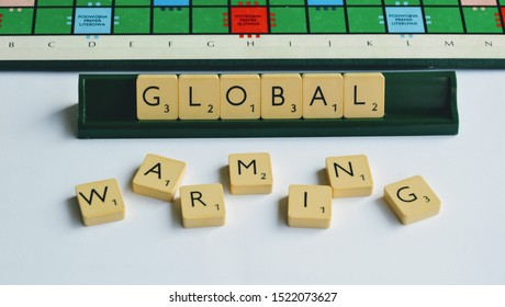 Warsaw, Poland - August 31 2019: GLOBAL WARMING words made from Scrabble game tiles. Scrabble letters spelling the message. Scrabble tiles on the stand. Ecology theme