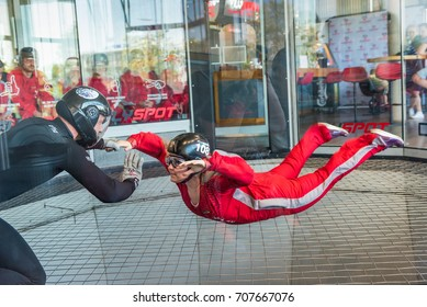 WARSAW, POLAND, AUGUST 5, 2017: Young women flying in an aerodynamic tunnel with trainer. Poland.