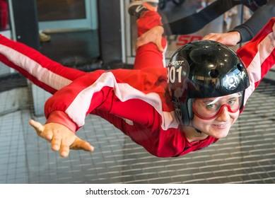 WARSAW, POLAND, AUGUST 5, 2017: Young woman enjoying flying in an aerodynamic tunnel.