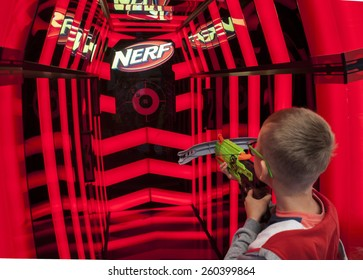 WARSAW, POLAND - AUGUST 8, 2014: Young boy playing Nerf toy gun in store.