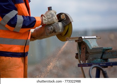 Warsaw, Poland, circa October 2015: An unidentified man dressed in high visibility protective clothing, uses an angle grinder. Strengthening Polish industry is a key priority for the new government.