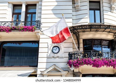 Warsaw, Poland Closeup of Polish red flag in old town historic street during sunny summer day and clock time