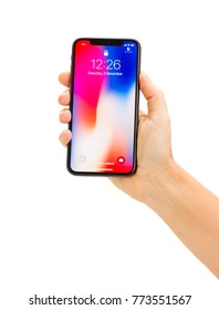 WARSAW, POLAND - DECEMBER 02: Hand holding new Iphone X mobile phone over white background