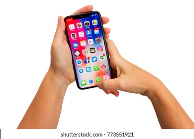 WARSAW, POLAND - DECEMBER 02: Two hands holding new Iphone X mobile phone with apps over white background