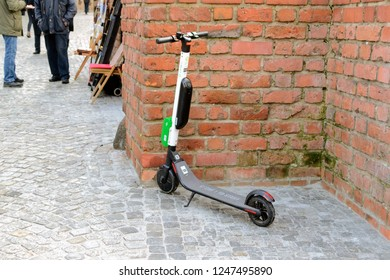 Warsaw, Poland - December 2 2018: A green Lime-S electric scooter for rent. Rental of new electric scooters in Warsaw. Electric scooter parked next to the brick wall at the Old Town in Warsaw