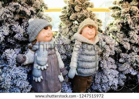 Warsaw, Poland - December 2 2018: Christmas decorations at Warsaw Christmas Market. Winter concept - figures of a boy and girl dressed in winter clothes